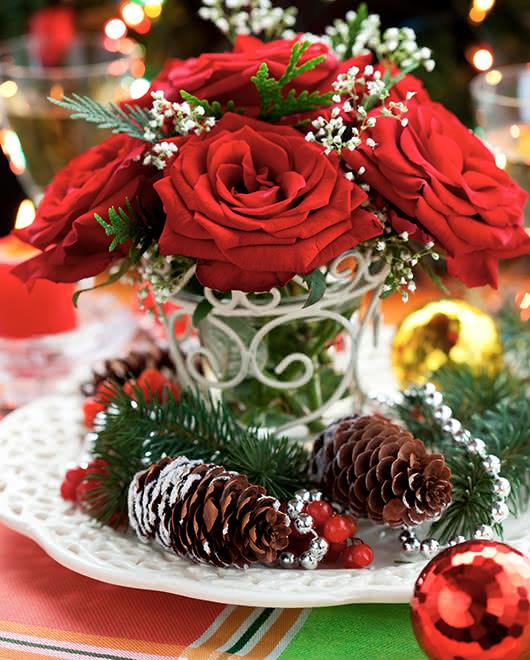 Arranjos florais de Natal em serviços de mesa, cadeiras e presentes